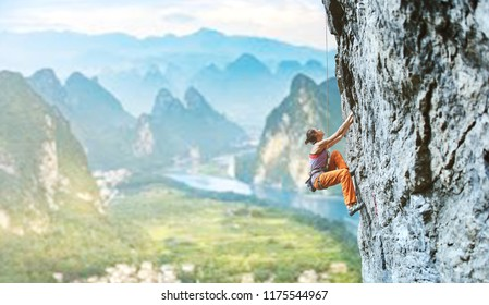 side view of young slim woman rock climber in bright orange pants climbing on the cliff against a high mountains. girl climbs on a vertical flat rocky wall and making hard move. Copy space