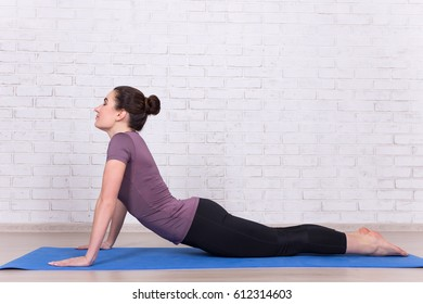 side view of young slim woman doing stretching exercises at home