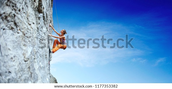 side view of young slim woman rock climber in bright orange pants climbing on the cliff. a woman climbs on a vertical rock wall on the blue sky background