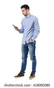 Side view of young smart casual business man reading message on cell phone. Full body length portrait isolated over white background.