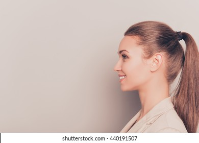 Side view of young smiling businesswoman isolated on gray background