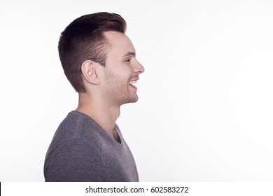 Side view of young smiling stylish man isolated on white background.
