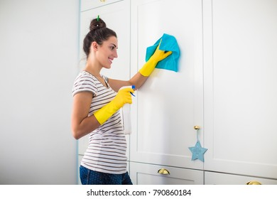 Side view of the young smiling woman in yellow gloves who holding rag and detergent in hands and washing furnitures in the room