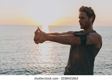 Side view young strong athletic toned fit sportsman man in sports clothes earphones mobile cell phone warm up train at sunrise sun dawn over sea beach outdoor on pier seaside in summer day morning.
