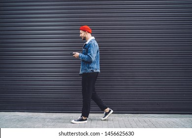 Side view of young stylish male in red cap and denim jacket walking on street and using mobile phone as GPS against garage background