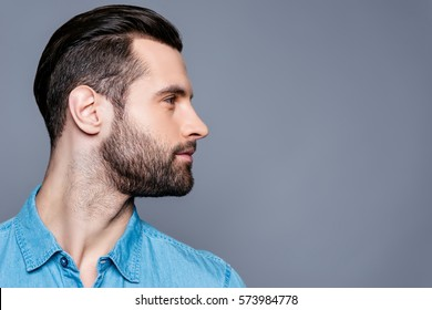 Side view of young stylish man isolated on gray background.