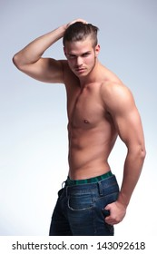 side view of a young topless man standing with his hand in his hair and the other in his back pocket while looking into the camera. on gray background