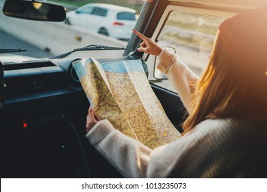 Side view of young traveler girl holding touristic map pointing finger right direction while riding in a vintage car, sunlight, lifestyle travel concept, woman enjoying vacation in Europe, flare light
