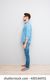 Side view of young trendy handsome man in glasses