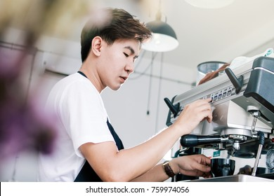Side view of young waiter making cup of coffee at coffee shop.