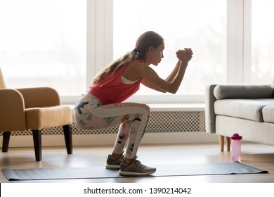 Side view young woman in activewear stands in sport mat do butt exercises deep static squat hold position improve body shape routine at home, healthy active lifestyle calories burn weight loss concept
