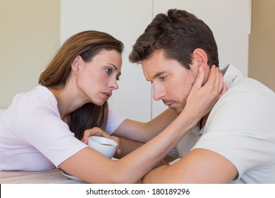 Side view of young woman consoling a sad man at home