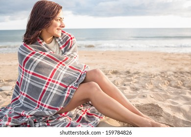 Side view of a young woman covered with blanket at the beach