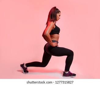 Side view, young woman doing legs exercise, studio shot