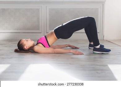 Side view of young woman doing gymnastics the half bridge pose in fitness studio or home practices yoga warming up exercises for spine, backbend, strengthening back and shoulders muscles.