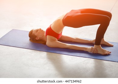 Side view of young woman doing gymnastics the half bridge pose in fitness studio or yoga warming up exercises for spine, backbend, strengthening back and shoulders muscles.