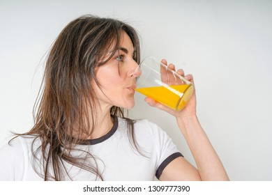 side view of young woman drinking orange juice isolated white background. healthy life concept