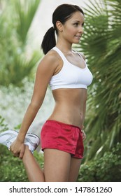 Side view of a young woman exercising in the park