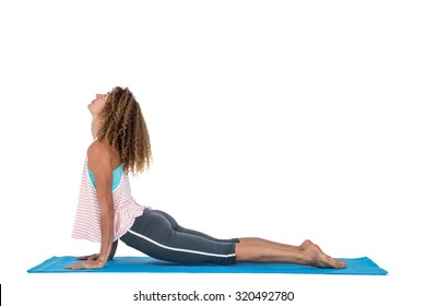 Side view of young woman exercising on mat against white background