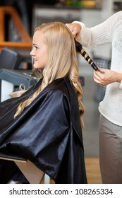 Side view of a young woman getting her hair curled by beautician at parlor