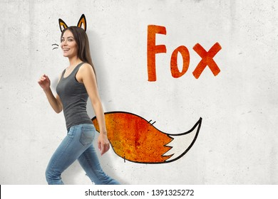 Side view of young woman in gray sleeveless top and blue jeans walking and smiling at camera against wall with fox ears and tail adds-on and title Fox . Playful mood. Good vibes. Character traits.