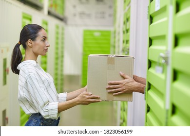 Side view at young woman holding cardboard box and handing in to man while packing self storage unit, copy space