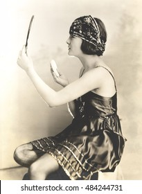 Side view of young woman holding powder puff and mirror