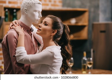 side view of young woman hugging layman doll at home, one way love concept