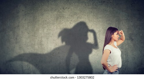 Side view of a young woman imagining to be a super hero looking aspired.