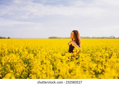 Side view of young woman with long hair touching her shoulder on yellow blooming rapeseed field