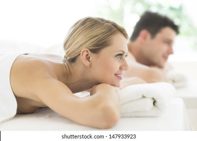 Side view of young woman looking away while relaxing at spa with man in background