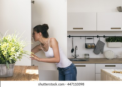 Side view of young woman looking for food in fridge