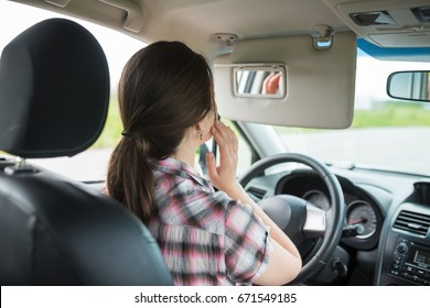 Side view of young woman looking at mirror and smiling while driving the car, Inattentive driving concept