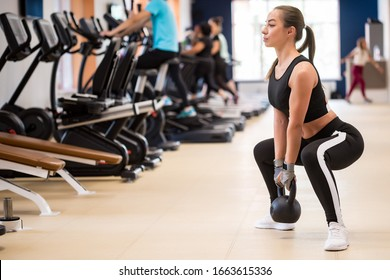 Side view young woman makes plie squats with dumbbell