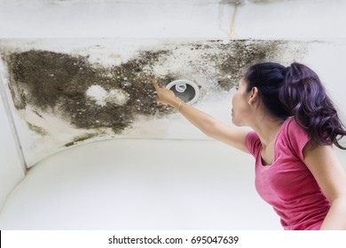 Side view of a young woman pointing at roof damage, caused by water leaks