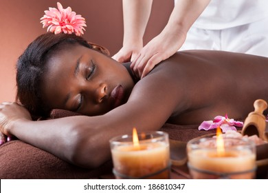 Side view of young woman receiving shoulder massage at spa salon