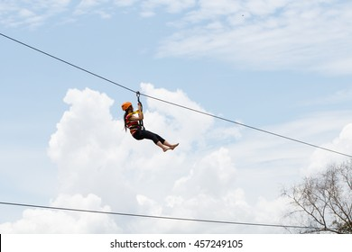 side view of young woman riding on zip line against sky