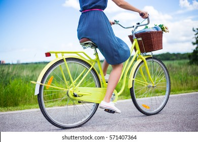 side view of young woman riding retro bicycle in countryside