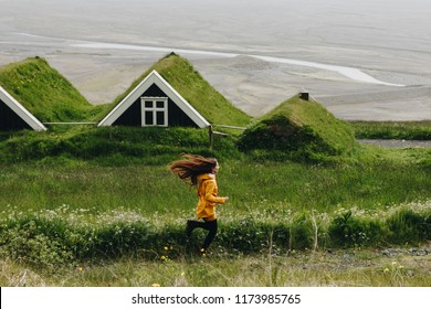 side view of young woman running near Black farmhouses in Skaftafell National Park