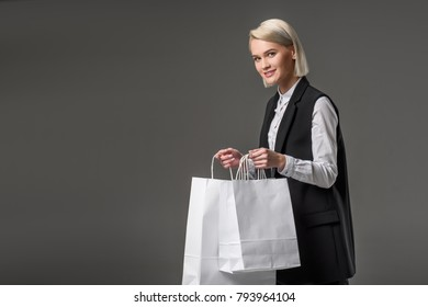 side view of young woman with shopping bags isolated on grey