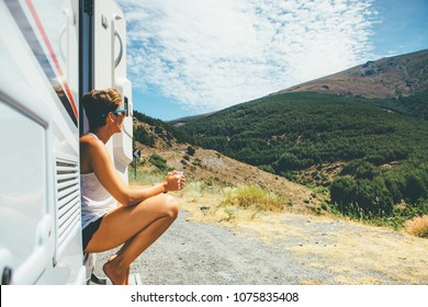 Side view of a young woman is sitting on a caravan step and holding a cup on a holiday adventure trip stop. Copy space area available
