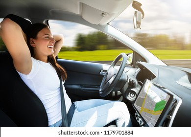 Side View Of A Young Woman Sitting In Self Driving Modern Car