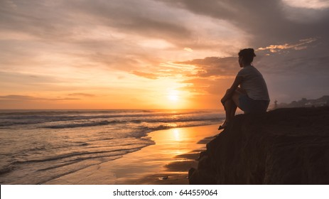 Side view of young woman sitting alone on the stone on ocean beach at sunset. Nobody around. Sunset reflects in the wet sand and sea water. Summer sea vacation, Canggu beach, Bali, Indonesia