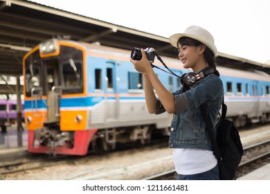Side view of young woman smile, tourist girl with backpack taking photo of train station landscape view and smile happily. at the railway station, Backpacker concept, vintage train,blurred background
