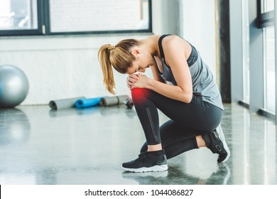 side view of young woman in sportswear having ache in knee while training in gym