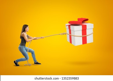 Side view of young woman standing with bent knees and pulling big gift box in air which she has lassoed, on yellow background. Bargain bin. Good eye for bargain. Get what you want.