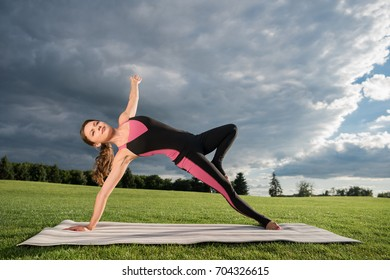 side view of young woman standing in wild thing yoga pose on yoga mat in park