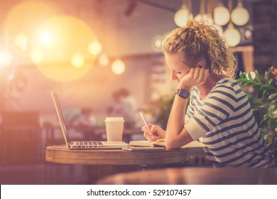 Side view. Young woman in striped blouse sitting at table in cafe and makes notes in notebook. In front of her is laptop next to cup of coffee. Online learning. Student doing homework. Film effect.