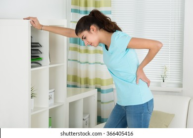 Side view of young woman suffering from backache leaning on shelves at home