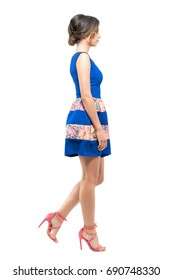 Side view of young woman in summer sleeveless blue short dress walking looking ahead. Full body length portrait isolated on white studio background.